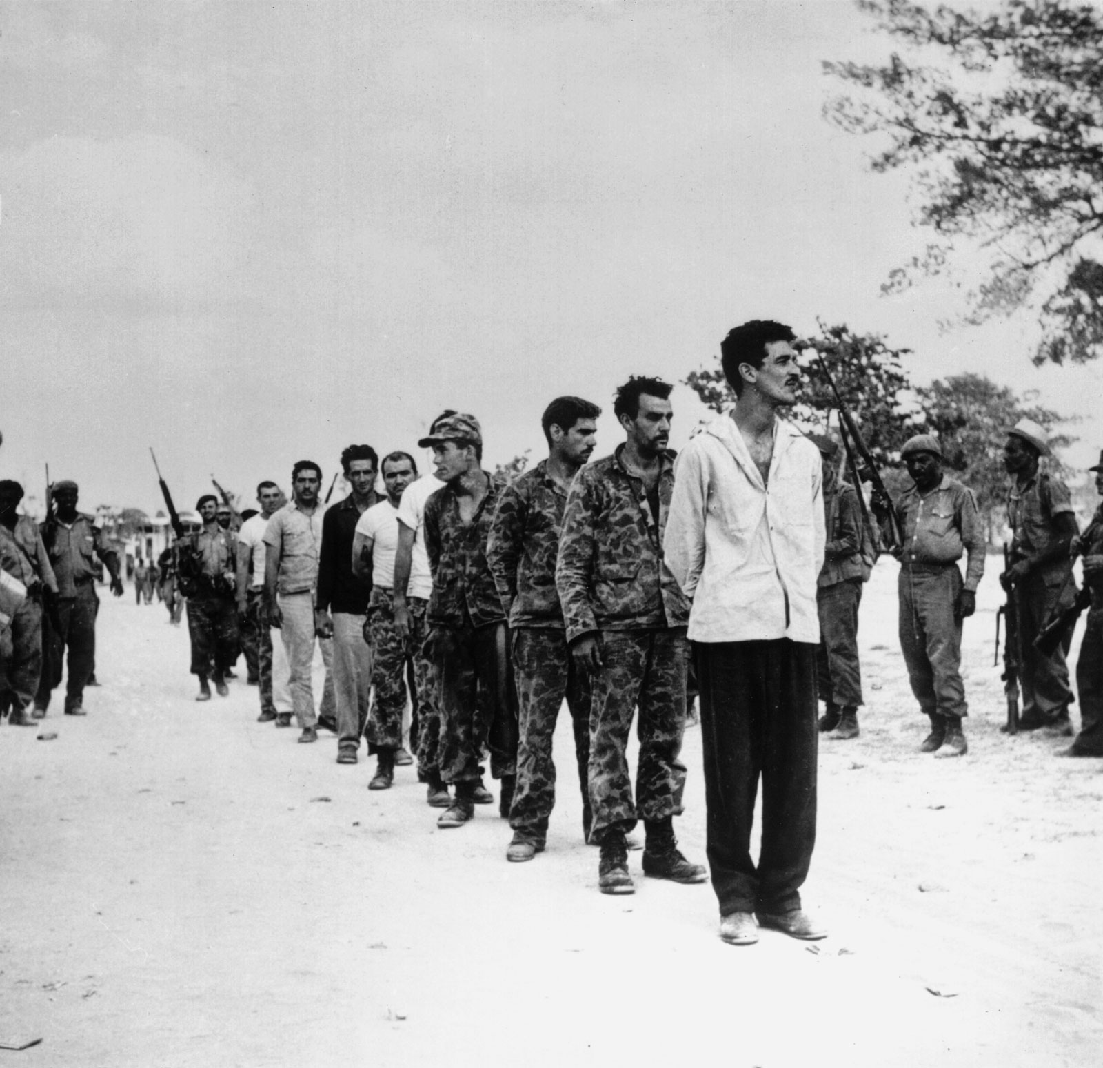 Captured Cuban exiles are lined up by Castro's soldiers at the Bay of Pigs